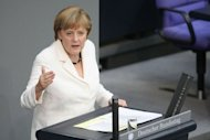 German Chancellor Angela Merkel addresses German lawmakers before they voted on the EU fiscal pact and permanent ESM bailout fund.The German parliament overwhelmingly approved two euro-crisis fighting tools Friday rallying to a call by Chancellor Angela Merkel to show the world Germany&#39;s commitment to the single currency