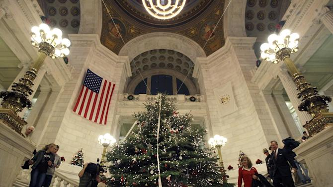 """People walk by a tree referred to as a """"holiday tree"""" by Gov. Lincoln Chafee in the rotunda of the statehouse in Providence, R.I. Tuesday, Dec. 6, 2011. The Rhode Island Statehouse hosted dueling tree lightings as Gov. Chafee and Republican State Rep. Doreen Costa battle over whether to call the official state spruce a """"holiday"""" tree or a """"Christmas"""" tree. The governor's decision to call the tree a 'holiday' tree prompted Costa to bring her own tree to the capitol. (AP Photo/Elise Amendola)"""