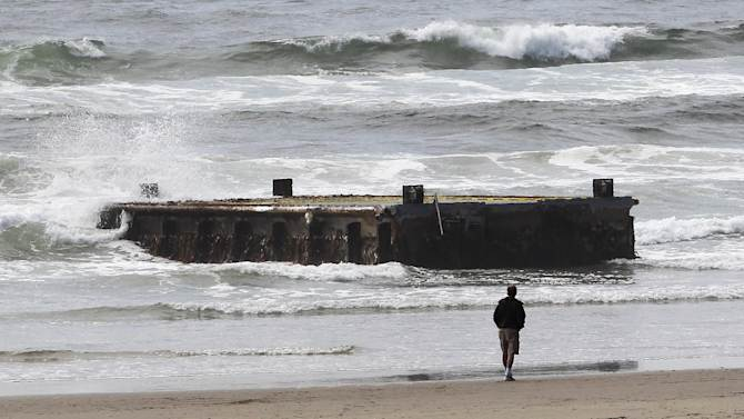 FILE -In this file photo from Wednesday, June 6, 2012, a man looks at a 70-foot-long dock with Japanese lettering that washed ashore on Agate Beach in Newport, Ore. The West Coast is anticipating more debris from the 2011 Japanese tsunami to wash ashore this winter. Scientists expect the bulk of the tsunami debris to end up in the Pacific Northwest. (AP Photo/Rick Bowmer, File)