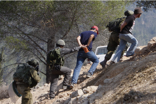 Israeli soldiers detain activists during a protest against the construction of Israel's separation barrier in the West Bank village of Walajeh, outside Jerusalem, Wednesday, Aug. 10, 2011. Israel says the barrier is necessary for security while Palestinians call it a land grab. (AP Photo/Nasser Shiyoukhi)