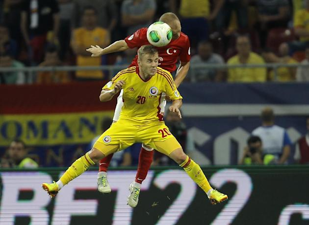 Turkey's Semih Kaya, rear, jumps for a header with Romania's Dragos Grigore during a World Cup Group D qualifying soccer match between Romania and Turkey at the National Arena stadium in Bucharest, Ro