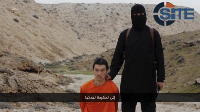 Still image of an Islamic State fighter standing next to a man kneeling on the ground purported to be Japanese journalist Kenji Goto in an unknown location