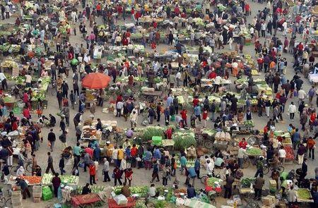 People buy vegetables at a morning market in Panjiayuan district, Beijing