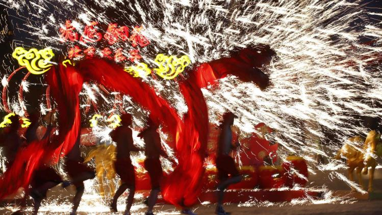 Dancers perform a fire dragon dance in the shower of molten iron spewing firework-like sparks during a folk art performance in Beijing
