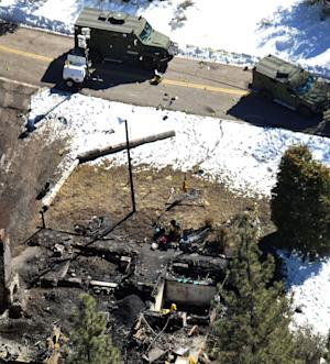 In this aerial photo, law enforcement authorities investigate the burnt-out cabin Wednesday, Feb. 13, 2013, where quadruple-murder suspect Christopher Dorner is believed to have died after barricading himself inside during a Tuesday stand-off with police in the Angeles Oaks area of Big Bear, Calif. San Bernardino Sheriff's Deputy Jeremiah MacKay was killed and another wounded during the shootout with Dorner. (AP Photo/The Sun, John Valenzuela)