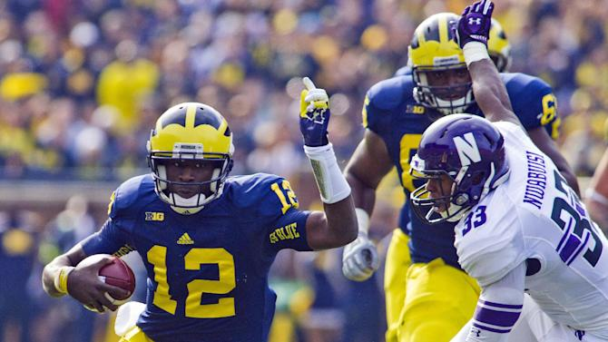 Michigan quarterback Devin Gardner (12) tries to evade Northwestern linebacker David Nwabuisi (33) during the second quarter of an NCAA college football game, Saturday, Nov. 10, 2012, in Ann Arbor, Mich. (AP Photo/Tony Ding)