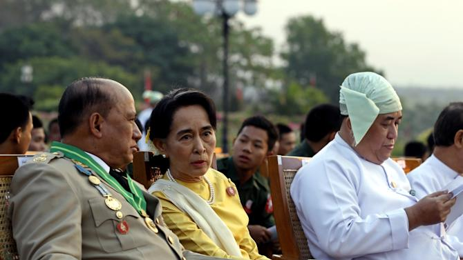 Opposition leader Aung San Suu Kyi, in yellow, talks with  Deputy Border Affairs Minister Maj. Gen. Zaw Win, left,  during Myanmar's 68th anniversary celebrations of Armed Forces Day, in Naypyidaw, Myanmar, Wednesday, March 27, 2013. The daughter of Aung San, Myanmar's most famous general and founding father, Suu Kyi has reached out to the military which was known for its brutality during its half-century of absolute rule over the objections of some in her own party. (AP Photo/Nyein Chan Naing, Pool)