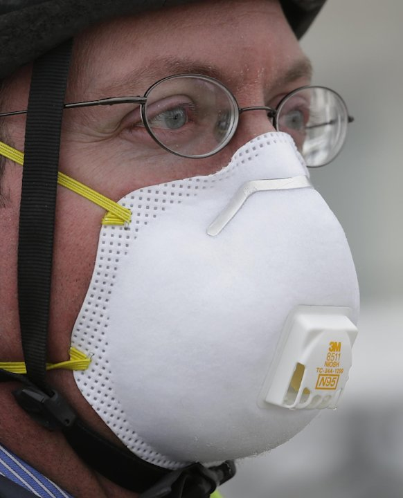 Dr. Gary Kunkel arrives at the Utah State Capitol wearing a breathing mask before a news conference Wednesday, Jan. 23, 2013, in Salt Lake City. A group of doctors is declaring a health emergency over
