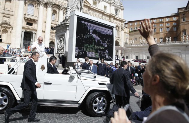 Pope Francis waves as he arrives to lead his Wednesday general audience in San Peter's square at the Vatican