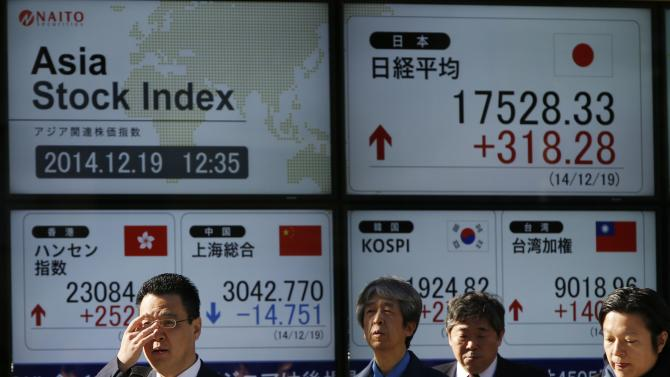 Passersby walk past an electronic board showing Japan's Nikkei share average and Asian countries' stock indexes outside a brokerage in Tokyo