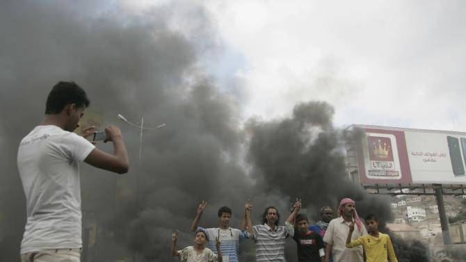 Supporters of the Southern Movement pose as a fellow protester takes a photo of them next to burning tyres during a protest in Yemen's southern port city of Aden