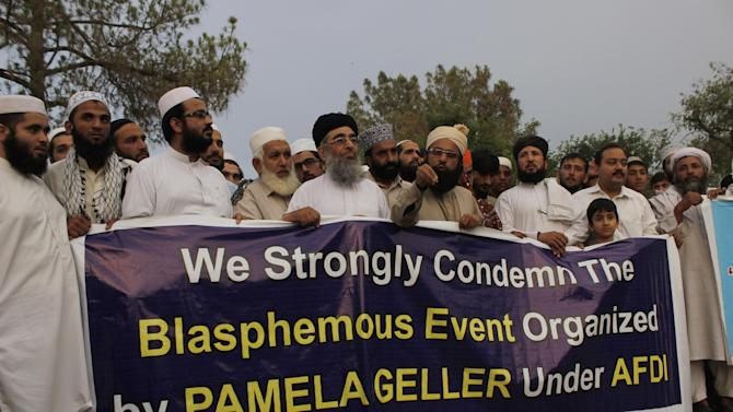 People hold a banner to condemn an organizer for a recent event in Texas, as they hold a special service at a public park in Peshawar, Pakistan, Tuesday, May 5, 2015. About 50 Islamists held the special service Tuesday in northwest Pakistan for two men killed in the U.S. state after they opened fire at a cartoon contest featuring images of the Muslim Prophet Muhammad. The cleric Mohammad Chishti led the service for Elton Simpson and Nadir Soofi. (AP Photo/Mohammad Sajjad)