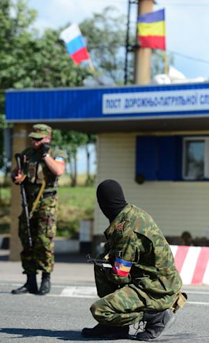 Pro-Russia armed separatists man a checkpoint, standing…