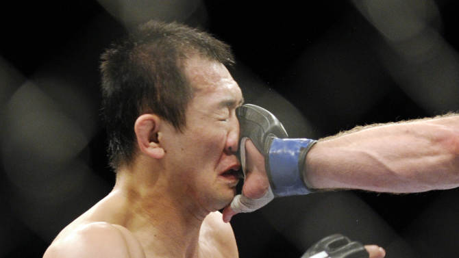 Yushin Okami of Japan takes a punch to the face by Alan Belcher of Biloxi, Miss. during their UFC 155 middleweight mixed martial arts match at the MGM Grand Garden Arena Saturday, Dec, 29, 2012 in Las  Vegas. Okami won the bout by an unanimous decision. (AP Photo/David Becker)