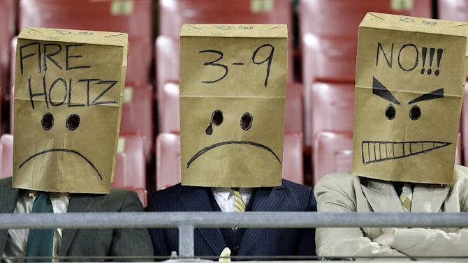 South Florida fans wear bags on their heads during the second half of an NCAA college football game against Pittsburgh Saturday, Dec. 1, 2012, in Tampa, Fla. Pittsburgh won the game 27-3. Pittsburgh defeated South Florida 27-3. (AP Photo/Chris O'Meara)