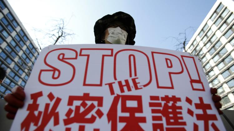 "A protester against the proposed state secrets act shows a banner saying ""Stop the state secrets act"" towards the parliament building in Tokyo"