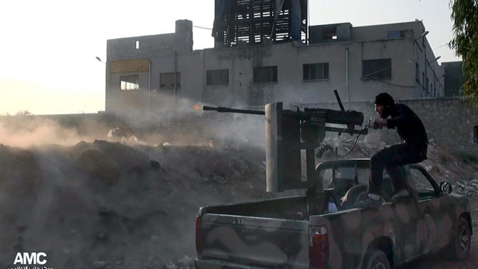 FILE - In this Saturday, Nov. 9, 2013 file citizen journalism image provided by Aleppo Media Center AMC, which has been authenticated based on its contents and other AP reporting, a Syrian rebel fires a weapon towards Syrian government troops loyal to President Bashar Assad in Aleppo, Syria. Syria's government and opposition will hold their first peace talks on Jan. 22 in Geneva, in an attempt to halt the nearly 3-year-old civil war that has killed more than 100,000 people, the United Nations announces. (AP Photo/Aleppo Media Center AMC, File)