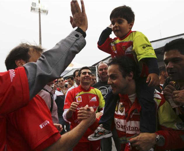 Felipe Massa of Brazil carries his son Felipe on his shoulders as he is greeted by fans after the Brazilian F1 Grand Prix at the Interlagos circuit in Sao Paulo