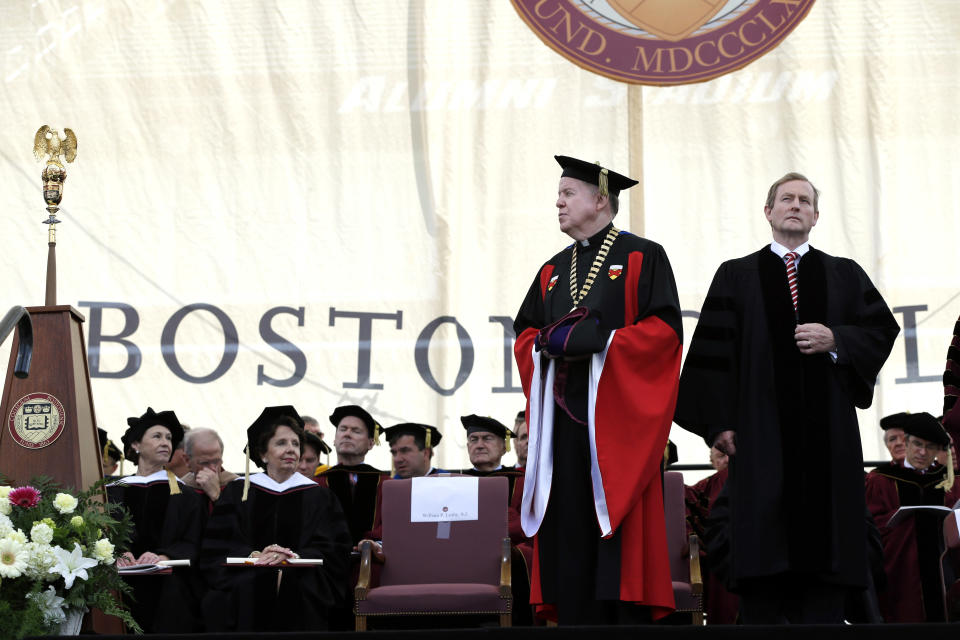 Irish Prime Minister Enda Kenny, right,  stands to receive an honorary Doctor of Laws degree from Boston College President William P. Leahy during commencement ceremonies at Alumni Stadium in Boston, Monday, May 20, 2013. (AP Photo/Elise Amendola)