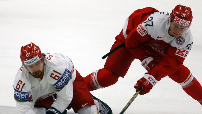 Stepanov of Belarus fights for the puck with Denmark's Poulsen during their Ice Hockey World Championship game at the CEZ arena in Ostrava