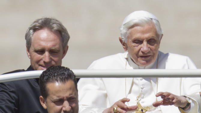 In this photo taken Wednesday, May, 23, 2012, Pope Benedict XVI, flanked by his private secretary Georg Gaenswein, top left, and his butler Paolo Gabiele arrives at St.Peter's square at the Vatican for a general audience. The Vatican has confirmed Saturday, May 26, 2012, Gabriele was arrested in an embarrassing leaks scandal. Spokesman the Rev. Federico Lombardi said Paolo Gabriele was arrested in his home inside Vatican City with secret documents in his possession. Gabriele, a layman, was being held. Vatican documents leaked to the press in recent months have pointed to power struggles and accusations of corruption touching senior Vatican cardinals. (AP Photo/Andrew Medichini)