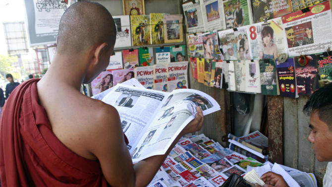 A Buddhist monk reads a journal at a roadside shop in Yangon, Myanmar, Tuesday, Feb. 28, 2012. Newspaper articles that would have been rejected by Myanmar's draconian state censors just months ago are making it into print, in one of many signs that the long-repressed country is becoming more open. Though censorship persists, especially on political issues, the government is allowing many stories to be published without prior review, and journalists who were once jailed, beaten or blacklisted are testing the new boundaries. (AP Photo/Khin Maung Win)