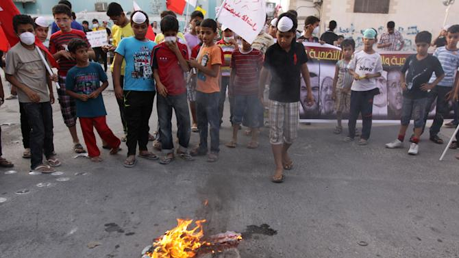 "In this photo taken May 17, 2012, Bahraini children watch as a representation of a U.S. flag set ablaze by anti-government protesters burns in the northern village of Diraz, Bahrain. During one of the nightly clashes with Bahrain's security forces, a new chant broke out among opposition protesters: ""The U.S. is the big devil."" A few days later, pro-government marchers also waved their fists against Washington. Both sides in the Bahrain meltdown are finding a shared target in the United States. (AP Photo/Hasan Jamali)"