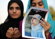 A Pakistani female activist of Islamic Minhaj-ul-Quran Party holds a photograph of child activist Malala Yousafzai as they pray for her recovery in Islamabad. The Pakistani schoolgirl shot in the head by the Taliban showed signs of improvement by moving her limbs Saturday, the military said, though she remains unconscious and on a ventilator