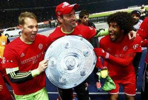 Bayern Munich's Neuer Starke and Dante celebrate winning Bundesliga title after German first division Bundesliga soccer match against Hertha Berlin in Berlin