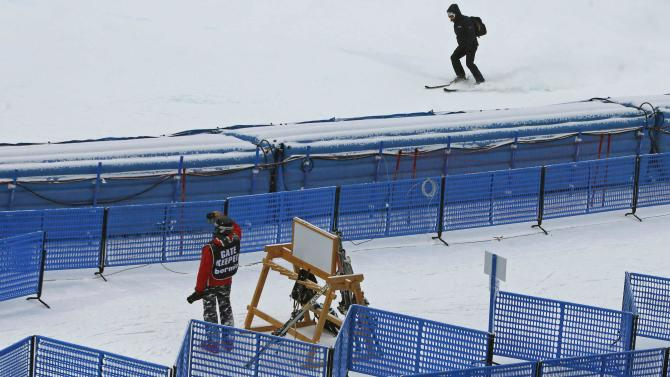 A gate keeper takes a picture of the men's World Cup Downhill skiing race track  in Santa Caterina