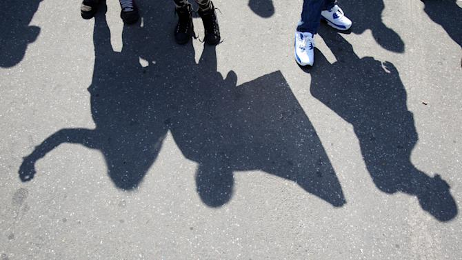 Shadows of protesters waving Serbian flags during the protest of Serbian nationalist organization Dveri, in Belgrade, Serbia, Sunday, April 21, 2013. Several hundred protesters gathered to protest against the recognition of Kosovo as an independent state. (AP Photo/Darko Vojinovic)