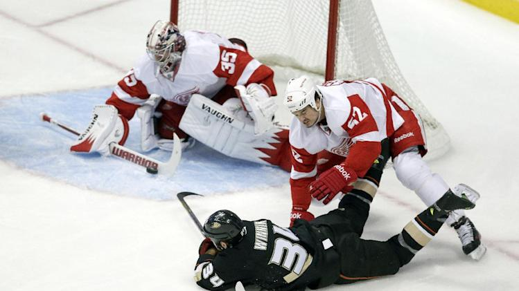 Detroit Red Wings goalie Jimmy Howard, top, blocks a shot from Anaheim Ducks center Daniel Winnik as Jonathan Ericsson helps on the play during the first period in Game 5 of their first-round NHL hockey Stanley Cup playoff series in Anaheim, Calif., Wednesday, May 8, 2013. (AP Photo/Chris Carlson)