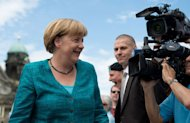 A cameraman films German chancellor Angela Merkel as she arrives for the German Christian Democratic Union CDU party meeting on June 23, 2013 in Berlin. Merkel's conservatives are trumpeting an electoral pledge to bump up child benefits but admit that the power of their family policy to boost the low birthrate that threatens to take the shine off the German economy is limited