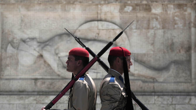 Greek presidential guards stand during the changing of the guards ceremony outside the Greek parliament in central Athens, Monday, July 9, 2012. A deputy labor minister has resigned from Greece's new coalition government, saying it should have pressed harder to renegotiate the terms of the country's bailout agreements. Nikos Nikolopoulos announced his resignation Monday, hours after the new conservative-led government won a confidence vote in parliament. (AP Photo/Dimitri Messinis)