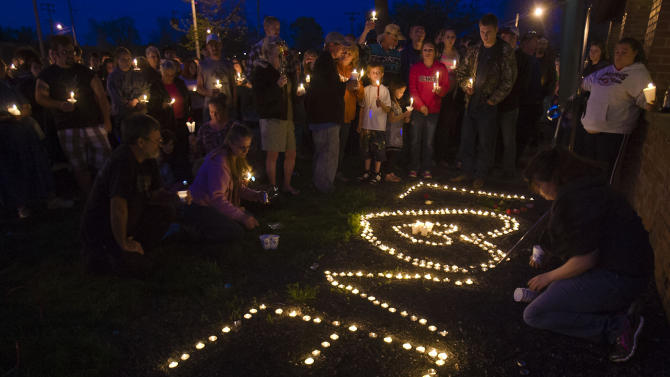 "People stand near candles that spell out ""love""  during a prayer vigil for Lana-Leigh Bailey and the other victims at Forest Park Friday, May 10, 2013 in Ottawa, Kan.  Kyle Flack, a 27-year-old convicted felon was charged Friday in the deaths of a woman and two men whose bodies were found at an eastern Kansas farm home earlier this week, according to a criminal complaint. (AP Photo/The Kansas City Star, Allison Long)"