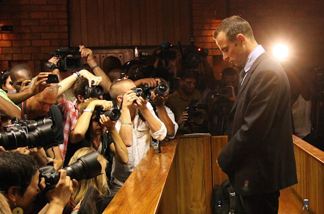 Photographers take photos of Olympic athlete Oscar Pistorius as he stands in the dock during his bail hearing at the magistrates court in Pretoria, South Africa, Friday, Feb. 22, 2013. The fourth and