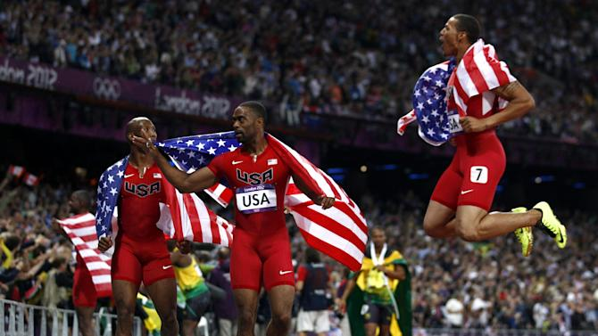 United States 4x100-meter relay runner Ryan Bailey, right, leaps in the air as he walks with teammates as Tyson Gay and Trell Kimmons, left, look on during the athletics in the Olympic Park during the 2012 Summer Olympics, Saturday, Aug. 11, 2012, in London. (AP Photo/Jon Super)
