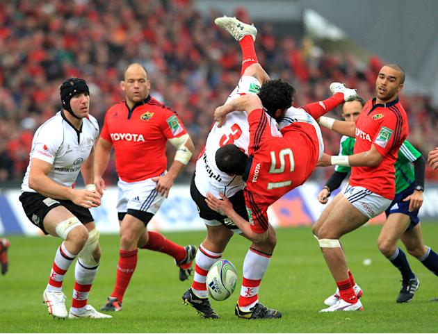 Munster's  Felix Jones (R) is up ended and loses control of the ball as he is tackled by Ulster's John Afoa (L) during the European Cup rugby union quarter final match between Munster and Ulster at th