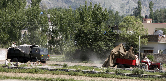 Vehicles carry the wreckage of a helicopter that crashed next to the wall of a compound where according to officials, Osama bin Laden was shot and killed in a firefight with U.S. forces in Abbottabad,