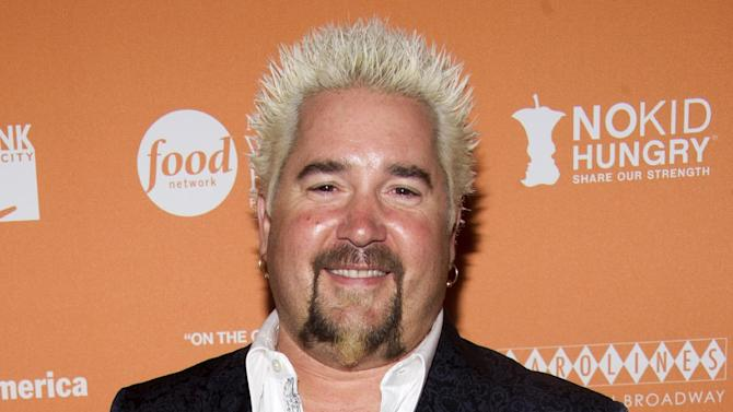 """FILE - This Oct. 11, 2012 file photo shows chef Guy Fieri at the """"On The Chopping Block: A Roast of Anthony Bourdain"""" in New York. New York Times reviewer Pete Wells scored a celeb smack down when he dissed Fieri's New York restaurant, Guy's American Kitchen & Bar, in a scathing 1,000-word review written entirely in questions. Wells took heat for beating on Food Network's bad boy, but the review, which tore across Twitter the instant it was posted, certainly drove hordes to Fieri's tables, even if only to rubberneck the culinary accident. (Photo by Charles Sykes/Invision/AP, File)"""