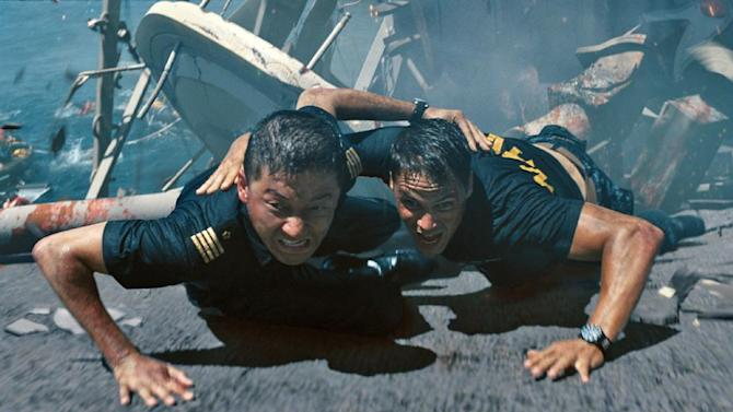 "In this film publicity image released by Universal Pictures, Tadanobu Asano, left, and Taylor Kitsch are shown in a scene from ""Battleship."" ""Battleship,"" a Universal Pictures movie based on the Hasbro Inc. board game, has survived an armada of tomato-throwing critics and chugged to $170 million in ticket sales overseas. The haul goes part way to justifying the reported $209-million price tag, but after subtracting splits with theater owners, it is estimated to need about half a billion at box offices to turn a profit. With a fleet of other hotly expected blockbusters surrounding its U.S. release on May 18, the tides need to be solidly in its favor to stay above water. (AP Photo/Universal Pictures)"