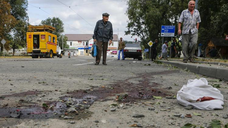 Residents walk past bloodstains on a road after, what locals say, was recent shelling by Ukrainian forces in Donetsk