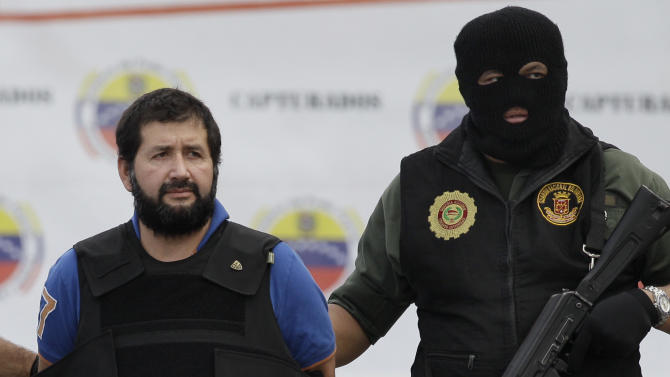 """Daniel Barrera Barrera, one of Colombia's most wanted drug lords, whose alias is """"El Loco Barrera,"""" is escorted in handcuffs and a flak jacket by National Guard officers as he is deported to Colombia from the Simon Bolivar airport in Maiquetia, near Caracas, Venezuela, Wednesday, Nov. 14, 2012. Barrera was captured on Sept. 18 in San Cristobal, Venezuela, near the border with Colombia. (AP Photo/Ariana Cubillos)"""