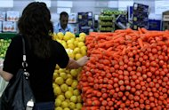 A woman shops for vegetables at a supermarket in Dubai