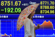 A woman walks in front of the electronic stock board of a securities firm in Tokyo Friday, Aug. 19, 2011. Asian stock markets were sharply lower Friday amid signs of a possible U.S. recession and renewed worries over the health of Europe's banks. Japan's Nikkei 225 index dropped 2.2 percent to 8,751.67 in the morning session. (AP Photo/Itsuo Inouye)