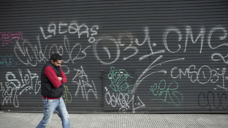 A man walks by shuttered stores during a strike in Buenos Aires, Argentina, Thursday, Aug. 28, 2014. The strike and protests over taxes, wages and the overall cost of living in the country, come amid deepening economic troubles for Argentina, with the economy in recession and inflation running around 40 percent. (AP Photo/Victor R. Caivano)