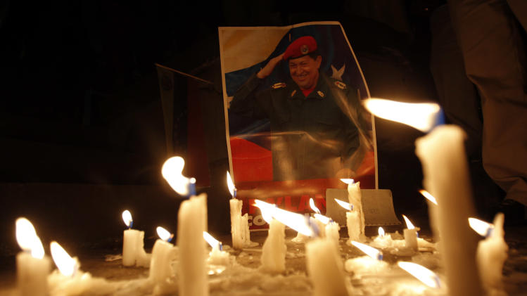 Candles, placed by mourner demonstrators, burn in front of an image of Venezuela's President Hugo Chavez outside Venezuela's embassy in Quito, Ecuador, Tuesday, March 5, 2013. Venezuela's Vice President Nicolas Maduro announced that Chavez died on Tuesday at age 58 after a nearly two-year bout with cancer. (AP Photo/Dolores Ochoa)