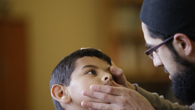 In this Friday, Dec. 18, 2015, photo Syrian refugee Ahmad Alkhalaf, 9, has his eye checked for an irritation by Na'eel Cajee at a mosque in Sharon, Mass. Ahmad, who arrived in the Boston area this past summer for medical treatment, said he used to have restless nights when he would relive his mother's screams from the night a bomb killed three of his siblings and left him without arms. But those sounds, he said, have largely faded. (AP Photo/Stephan Savoia)