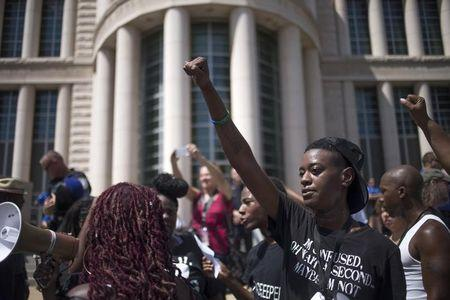 Activists raise their hands as they demand justice for the killing of Michael Brown after marching to the Thomas F. Eagleton United States Courthouse from City Hall in downtown St. Louis, Missouri