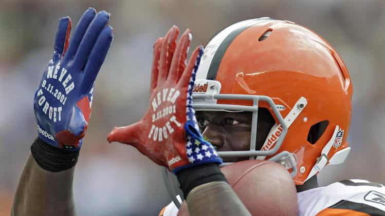 """Cleveland Browns tight end Benjamin Watson flashes """"Never Forget,"""" in a reference to Sept. 11, 2001, on his gloves after catching a 34-yard touchdown pass against the Cincinnati Bengals in the second quarter of an NFL football game Sunday, Sept. 11, 2011, in Cleveland. (AP Photo/Tony Dejak)"""